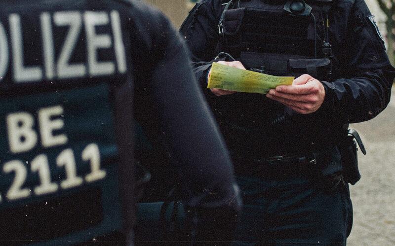 Polizist liest Fahrzeugpapiere
